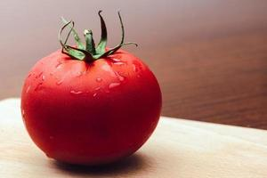 Red tomato on a cutting board on the wooden background. Copy space. Fresh tomato for cooking. Tomato with droplets of water. photo