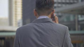 Asian businessman walking and using smartphone. Slow motion portrait asian businessman answers the phone. Asian man with glasses use phone in street near big office building. video