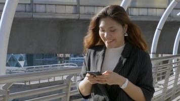 Smiling young asian woman walking texting on smartphone at urban city background video