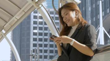 Smiling young asian woman texting on smartphone at urban city background video