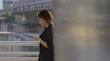 Young asian woman walking texting on smartphone at urban city background, Searching for social media. video