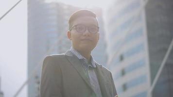 retrato apuesto hombre de negocios asiático sonriendo y mirando a la cámara de pie en la ciudad urbana. Hombre asiático con gafas en la calle cerca del gran edificio de oficinas. disparar a cámara lenta en ángulo bajo. video