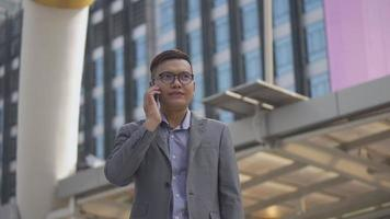 Slow motion portrait asian businessman answers the phone. video