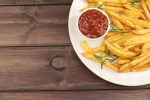 plato con deliciosas papas fritas y salsa de tomate foto