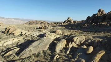 Aerial shot of a young man backpacker standing on a boulder with his dog in a desert mountain range. video