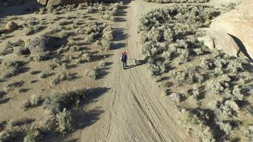 Aerial shot of a young man backpacking with his dog on a dirt road in a mountainous desert. video