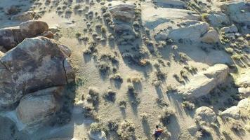 Aerial shot of a young man backpacking with his dog in a desert. video
