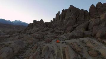 Aerial shot of a young man backpacker camping with his dog in a mountainous desert. video