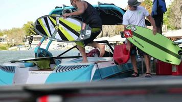 A man fills up his boat with gasoline before wakeboarding wake surfing. video