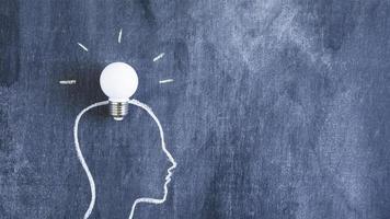 White light bulb on head outline on a chalkboard photo