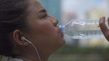 Close up portrait young asian woman runner drink water after running. Sports woman running healthy lifestyle. video