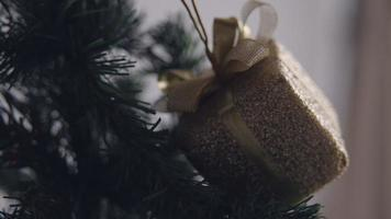 Golden box Christmas ornament hanging on a dry tree branch. 4K handheld shooting. video