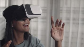 Close up attractive portrait beautiful young asian woman playing game and watching movie in vr glasses. Happy asian girl using 3D virtual reality headset at home. video