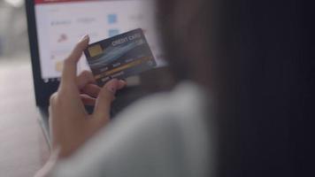 bouchent les mains jeune femme asiatique tenant une carte de crédit à l'aide d'un ordinateur portable faisant des achats en ligne à la maison. video