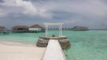 arco branco com bangalô e fundo do mar nas maldivas video