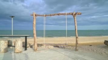 wooden swing on beach with oceans background video