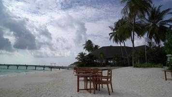empty table and chair for dinner on beach in Maldives video