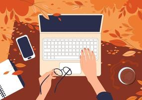 Top view on female hands working behind a laptop on the grass in an autumn park. Flat vector illustration of freelance outdoors