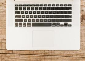 Laptop keyboard on wooden background photo
