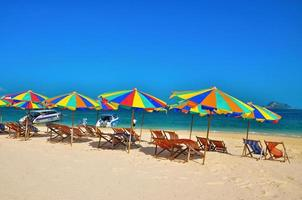 Phuket, Thailand, 2020 - Chairs and colorful umbrellas on a beach photo