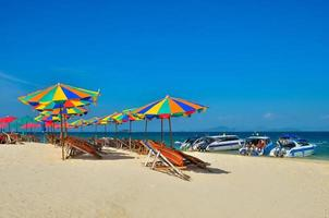 Phuket, Thailand, 2020 - Chairs and umbrellas on a beach with people and boats photo