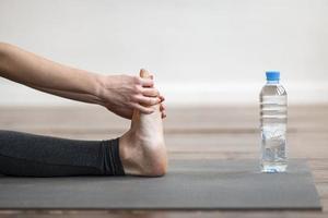 Woman stretching on yoga mat photo