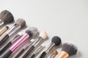 Pinceles de maquillaje dispuestos en una fila sobre fondo blanco. foto