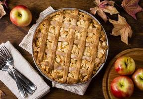 Apple pie for thanksgiving with cutlery and autumn leaves photo