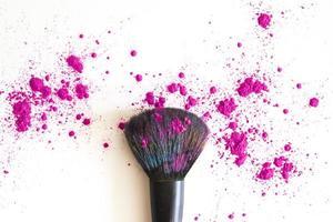 pincel de maquillaje y polvos rosados para la cara foto