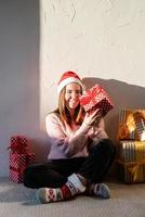 Young woman in santa hat surrounded by presents photo