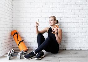 woman doing selfie after workout sitting at the floor photo