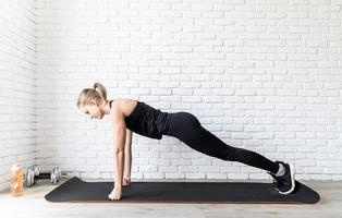 woman in black sportswear doing push ups at home photo
