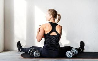 woman working out with dumbbells showing her back and arms muscles photo