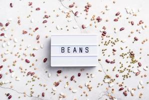 legumes with lightbox with the text Beans top view flat lay photo