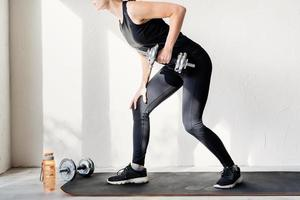 woman working out doing dumbbell lifts training her back and arms photo