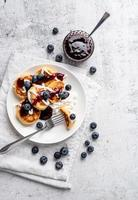 cottage cheese pancakes with sour cream, blueberry jam and blueberries photo
