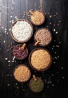 legumes in wooden bowls top view flat lay on wooden background photo