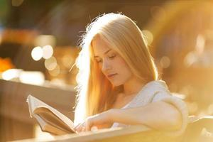 Happy blonde girl reading a book photo
