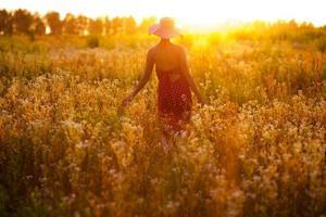 niña de flores silvestres en una tarde de verano foto