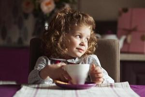 Little curly-haired girl with a cup photo