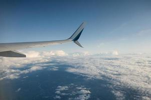 View of wing airplane on cloudy in blue sky photo