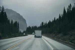 Road trip with car driving in pine forest with rocky mountains on gloomy at Banff National Park photo