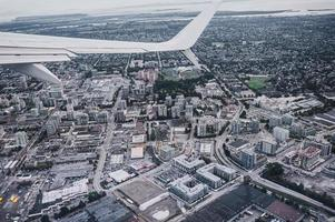 Aerial view of airplane wing on traffic in crowded city photo
