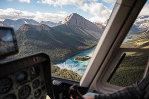 Inside of helicopter flying on rocky mountains with colorful lake photo