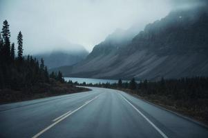 Mysterious road trip with rocky mountains in misty on gloomy at Banff national park photo