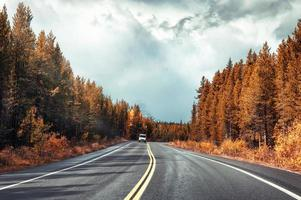 Asphalt highway in colorful autumn forest and overcast sky at Banff national park photo