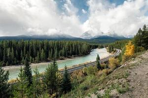 Railway with rocky mountains and cloudy in autumn valley at Morant's Curve photo