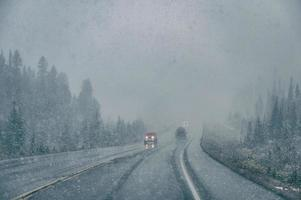 Car driving with poor visibility in blizzard with heavy snowing photo