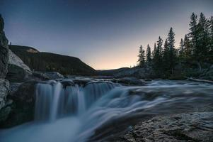 Waterfall rapids flowing on rocks in pine forest on evening at Elbow falls photo