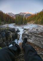 Legs traveler sit stretching on Sunwapta Falls in Icefields Parway at Jasper national park photo
